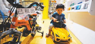 一位小朋友在某租赁平台线下体验区试玩新玩具。人民视觉