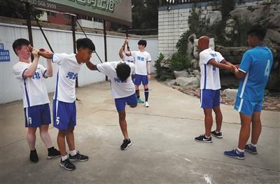 早餐前,队员跑完步后,相互帮助做拉伸运动。