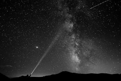 8月12日,在马其顿马夫罗沃国家公园,一名男子用灯指着夜空中的银河系。新华社/路透