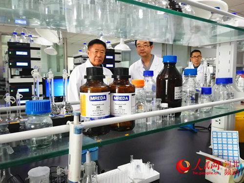 图为常山药业研究院,高树华(左一)与科研人员交流。杨文娟摄