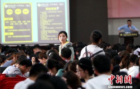 两个女孩在拥挤的教室里寻找座位。 张道正 摄