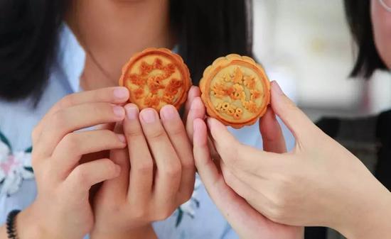 """△浙江农林大学""""校徽""""版月饼。据介绍,该校推出的校徽月饼,有豆沙、哈密瓜等各种口味供师生选择,让师生在品尝月饼的同时,也能感受学校的精神文化底蕴。"""