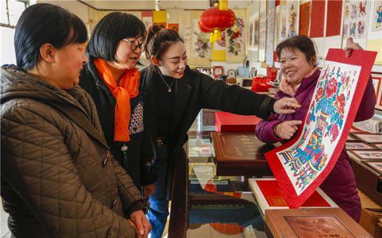 1月18日,游客在河北省武强县的年画礼品店选购年画产品。
