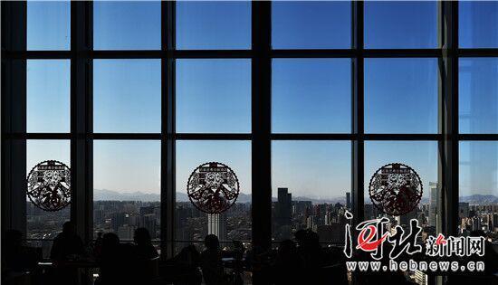 2月12日,从石家庄希尔顿酒店自助餐厅向外望去,湛蓝的天空映衬着喜庆的窗花,远山清晰可见。 记者赵海江摄