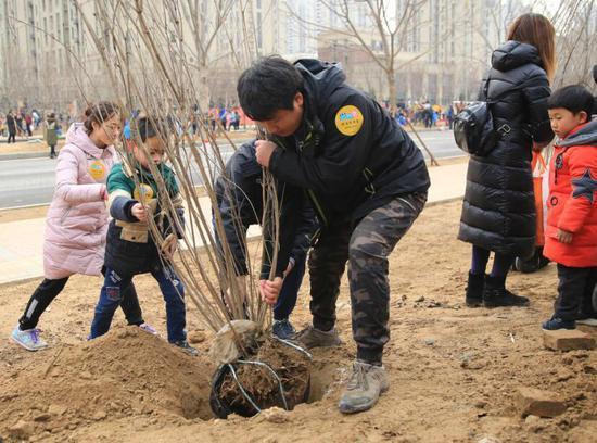 3月11日,小朋友和家长一起在固安县产业新城参加植树活动。新华社发(门丛硕摄)