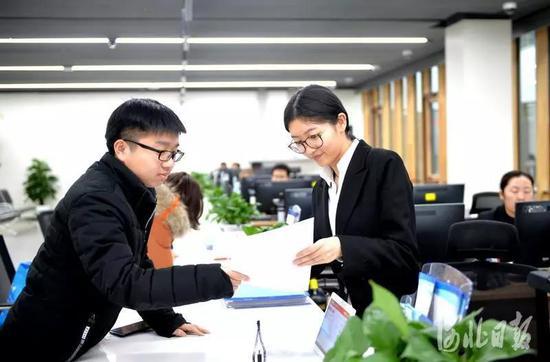 在雄安新区政务服务中心,工作人员(右)正在为市民办理企业注册手续。(资料片) 河北日报客户端记者陈建宇摄