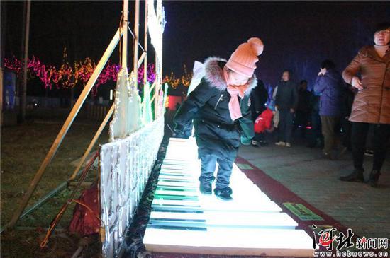在北戴河第七届春节灯会中,小朋友在灯光钢琴上嬉戏玩耍。 记者孙也达摄