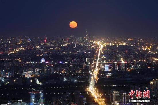 10月2日,中秋国庆假期第二天,北京天气晴好,一轮明月在夜晚逐渐升起。中新社记者 盛佳鹏 摄