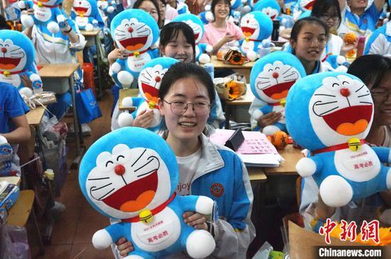 图为6月5日,河南郑州市第四中学高三学子展示收到的哆啦A梦公仔。 中新社记者 韩章云 摄
