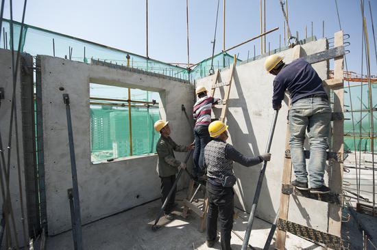 图为工人们正在将外墙板固定在对应位置 崔炜摄