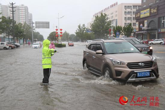 图为8月12日7点40分,任丘交警雨中疏通交通。