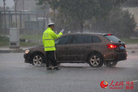 图为8月11日,沧州任丘交警雨中疏通交通。