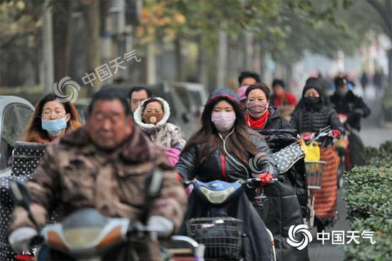 (13日早晨,石家庄空气质量下降,外出市民佩戴口罩防护)