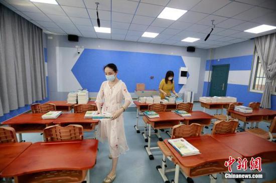 图为武汉市楚才中学的老师正在分发新学期课本。 王方 摄