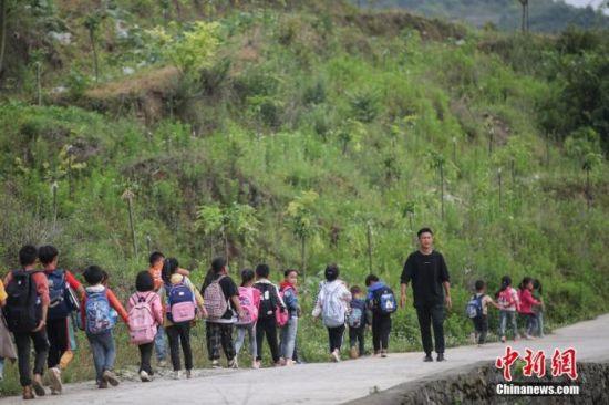 """资料图:一名""""90后""""乡村教师组织学生排队上下学。 中新社记者 瞿宏伦 摄"""