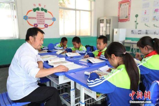 资料图:甘肃省庆阳市镇原县方山乡贾山家长学校,老师正在给学生们上课。 中新社记者 于晶 摄