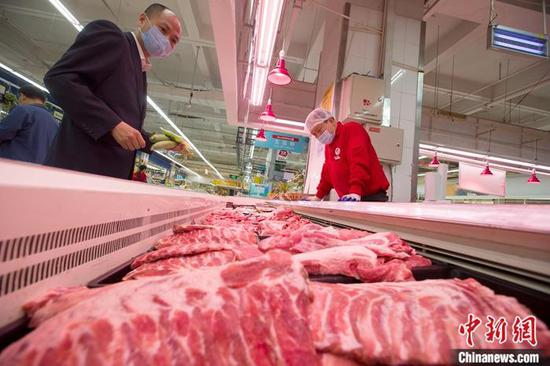 资料图:山西省太原市一超市,消费者正在选购猪肉。中新社记者 张云 摄