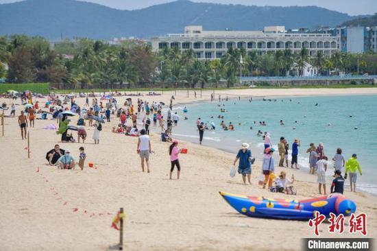 图为三亚大东海旅游景区的沙滩吸引了许多游客前来游玩,享受阳光沙滩。 骆云飞 摄