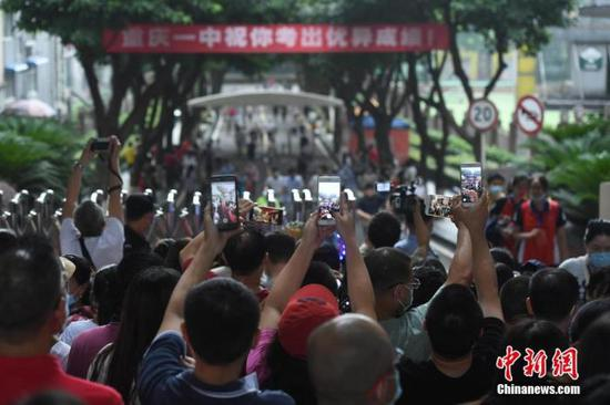 资料图:2020年7月7日,重庆市第一中学校考点,家长迎接孩子。 中新社记者 陈超 摄