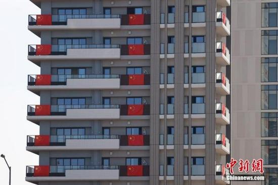 资料图:当地时间7月19日,记者探访东京奥运会奥运村广场。图为中国奥运代表团入住的房间阳台悬挂中国国旗。 中新社记者 富田 摄