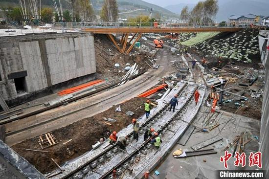 图为9月15日,建设工人正在太子城冰雪小镇有轨电车线路处施工。 翟羽佳 摄