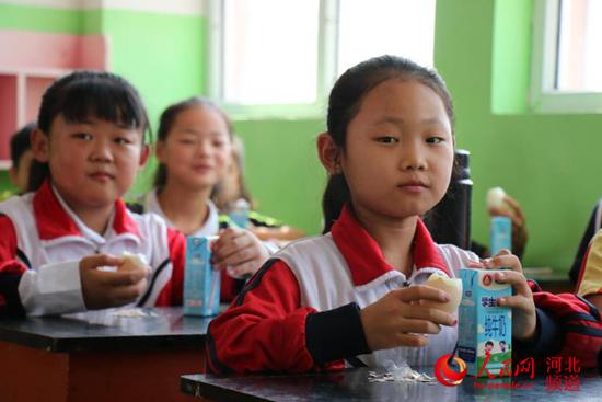 """图为9月5日,河北省邯郸市广平县十里铺中心小学学生课间吃上了""""免费加餐""""牛奶、鸡蛋。"""