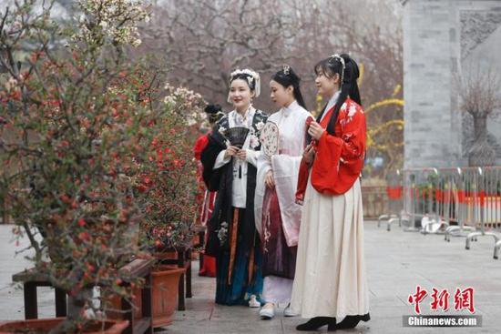 资料图:3月26日,身着汉服的女孩在北京陶然亭公园欣赏海棠花。 中新社记者 杜洋 摄