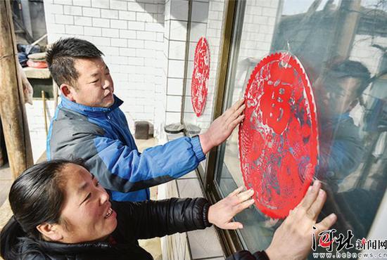 脱贫户范凤琴夫妻贴窗花,迎新春。