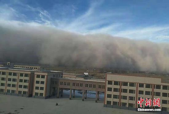 图为沙尘暴逐渐覆盖城市。