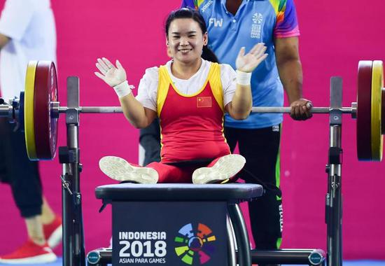 10月7日,郭玲玲在比赛后庆祝胜利。当日,在雅加达举办的第三届亚洲残疾人运动会女子举重45公斤级比赛中,中国选手郭玲玲以115公斤的成绩夺冠,并创造了新的世界纪录。新华社记者杜宇摄