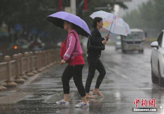 资料图:民众冒雨在北京街头出行。中新社记者 杨可佳 摄