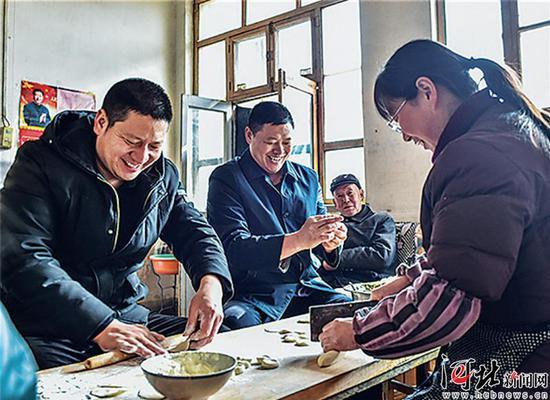 驻村工作组与脱贫户一起包饺子过大年。