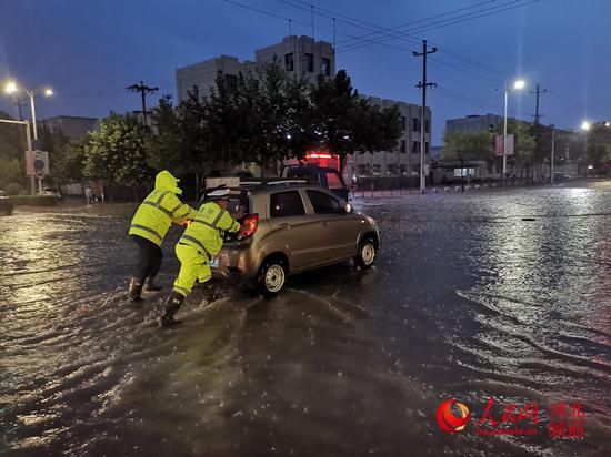 图为8月11日19点30分,在吴桥县钱塘江路与华山道交叉口,一线交警在暴雨中将抛锚车辆推至安全地带。