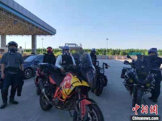 民警让5位车主将摩托车推至收费站外接受检查。 刘文杰 摄