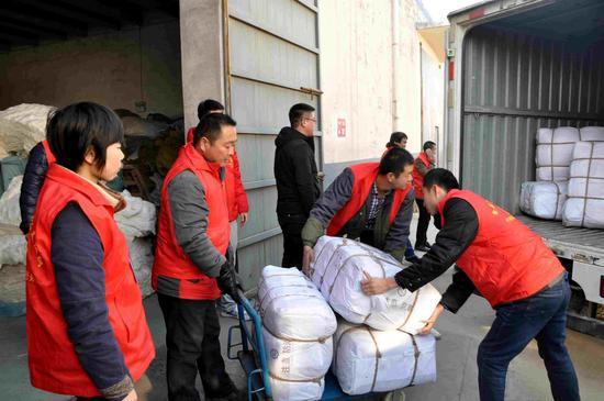 红十字志愿者将2600件棉大衣装车