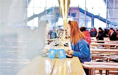 12月15日,石家庄火车站售票大厅,一名乘客正在用支付宝软件购买车票。 记者赵威摄
