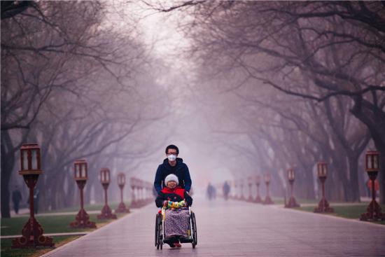 12月17日,市民行走在北京天坛公园。16日,北京市启动2016年首个重污染天气红色预警。新华社发