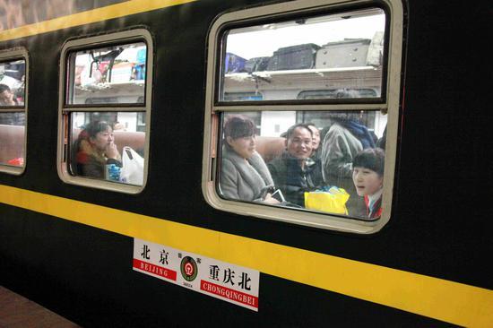 图为:乘坐首趟加开旅客列车离京回家的人们。摄影:李溢春