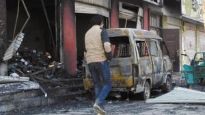 ■发生爆炸的店铺,门前汽车也被烧毁。本报记者 王彬 摄