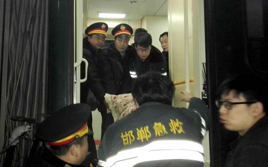 列车工作人员与急救中心医护人员一起抬旅客下车。