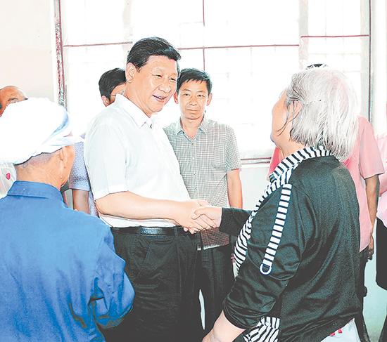 2013年7月11日至12日,中共中央总书记、国家主席、中央军委主席习近平在河北省调研指导党的群众路线教育实践活动。这是习近平在平山县西柏坡革命旧址同当地群众握手交谈。(资料片) 新华社发