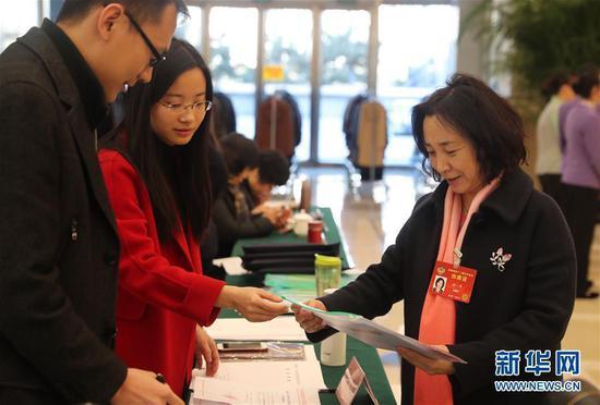 全国政协委员姚一萍(右)抵达驻地北京会议中心。