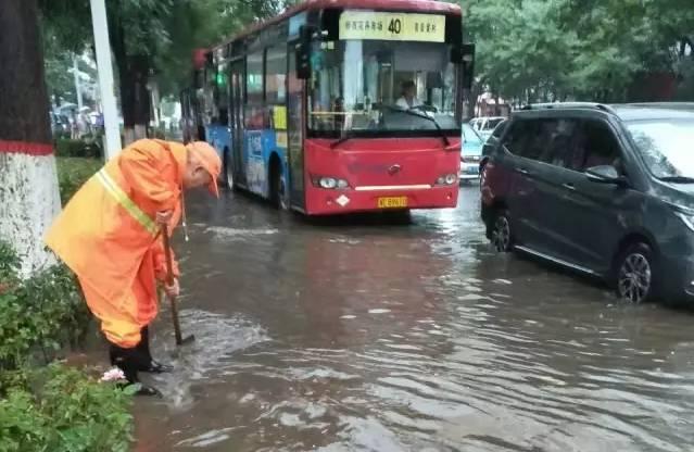 邢台环卫工冒雨清理排水管道