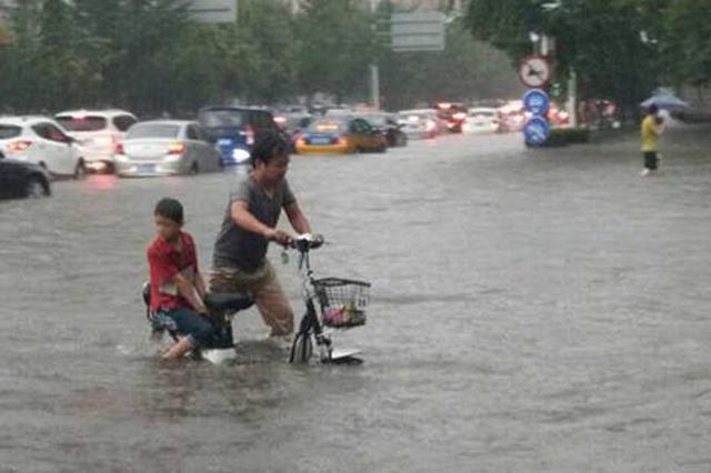 石家庄大雨部分路段水深过膝 交警雨中推车