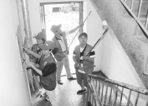 党员志愿者清理小区小广告。本报记者 郄磊 摄