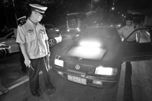 在谈固北大街与北二环交口附近,民警正在检查这辆加装了强光光源的轿车。 本报首席记者 李青 摄