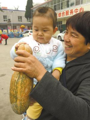 ■一位社区居民带着小朋友来买瓜。