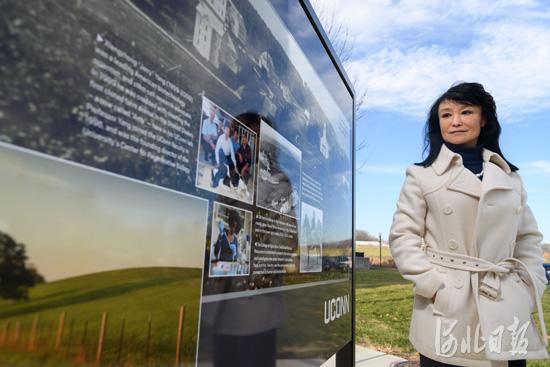 杨向中的妻子田秀春在康州大学校内关于杨向中的宣传牌前伫立。