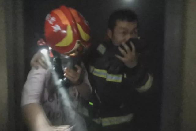 烈火浓烟中,消防员将自己的呼吸面罩让给被困者