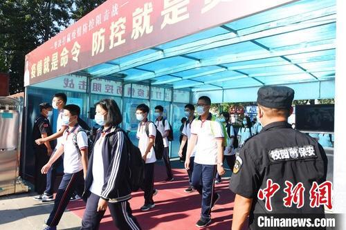 9月1日,在河北省廊坊市第六中学,学生通过体温移动检测系统进入学校。 宋敏涛 摄